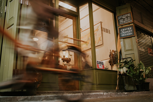 on the move, passing coffee shop in the evening