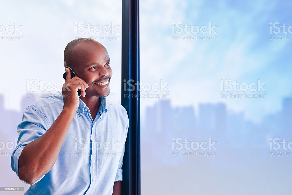 On the phone Smiling man talking on the smart phone in the office. Adult Stock Photo