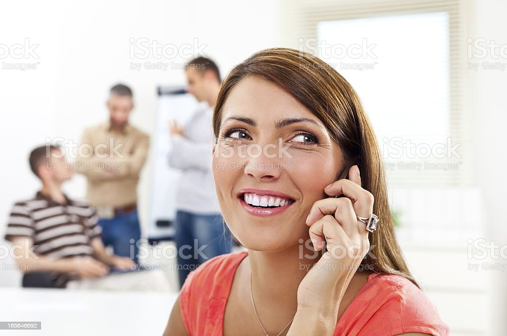 On the phone Happy woman talking on phone in an office, while her colleagues discussing in the background. 30-34 Years Stock Photo