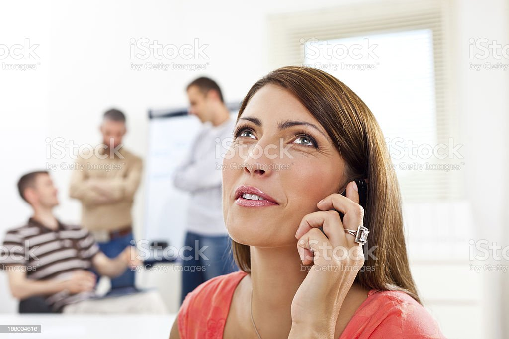 On the phone Smiling woman talking on phone in an office, while her colleagues discussing in the background. 30-34 Years Stock Photo