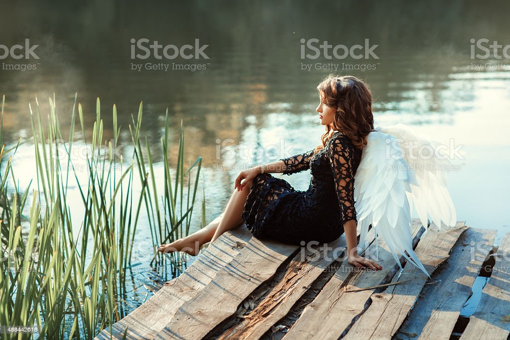 On the pier near  river sits a girl angel. stock photo