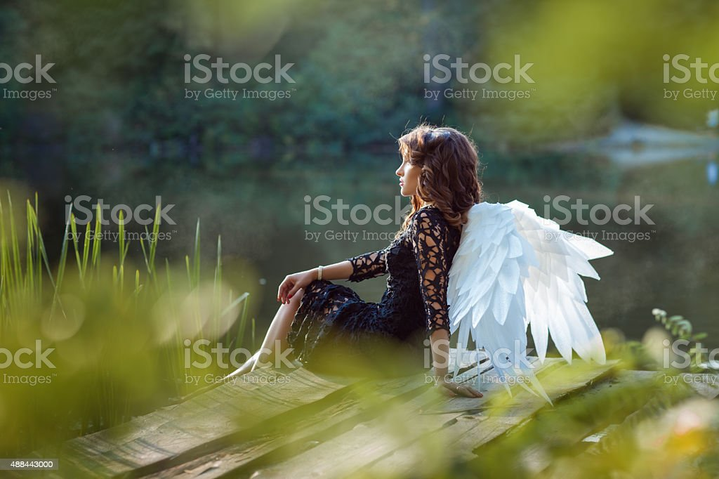 On the pier sits angel girl. stock photo