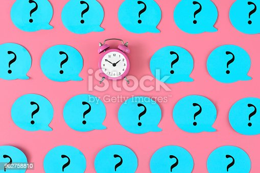 istock On the pink background is a alarm clock. Around him are glued many blue stickers with question marks. Concept, a matter of time. 962758810