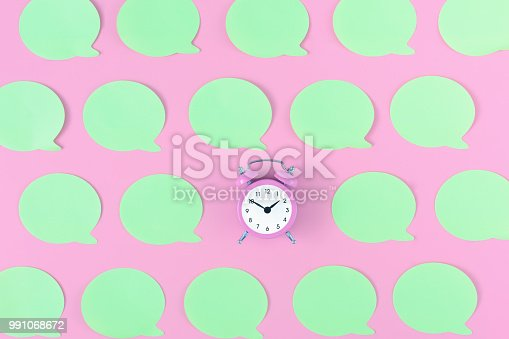 istock On the pink background is a small pink alarm clock. Around it are glued empty light green stickers. Bright photo on top, layout. 991068672
