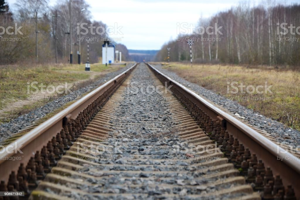 In the foreground is a crushed stone on the railroad track, a piece...