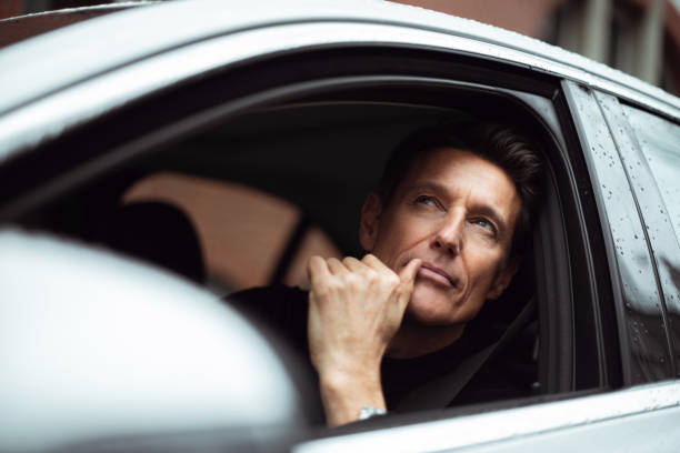 On the right place Handsome 55-year-old man is looking through the window of his car. georgijevic frankfurt stock pictures, royalty-free photos & images