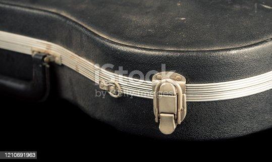 A worn violin case shot against a black background