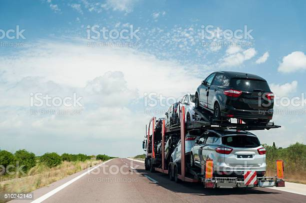 Articulated truck transport of automobiles driving on the road.