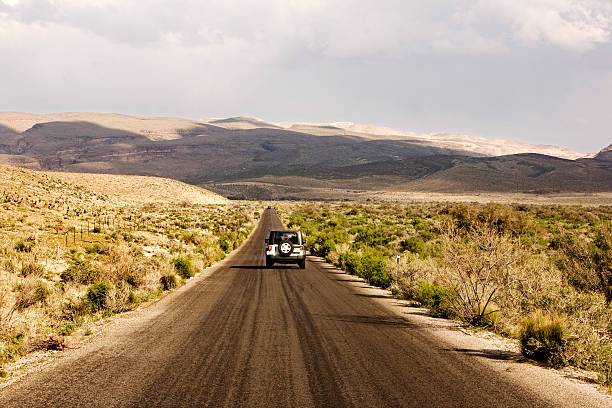 On the road Crossing the Nevada desert in a four wheel steering car. middle of the road stock pictures, royalty-free photos & images