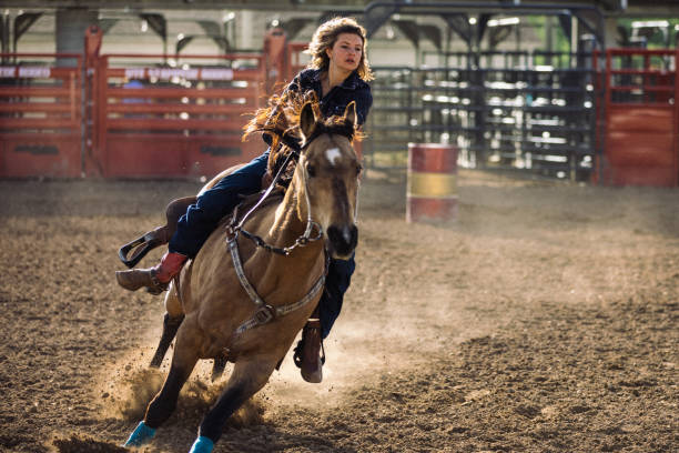 On the rodeo grounds, a teenage cowgirl on her horse during the barrel racing competition. stock photo