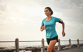 Shot of a young woman running on the promenade