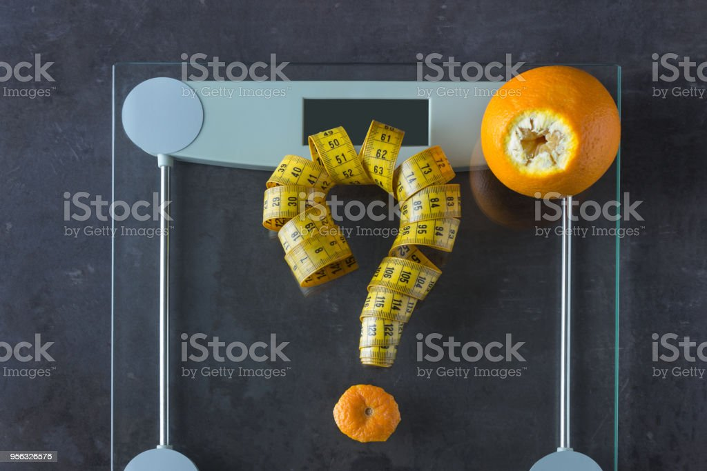 On the scales is measuring tape and fruit orange. Symbol-  question mark. Concept- lifestyle, sports and diet for weight loss. stock photo
