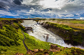 Fantastic Golden Waterfall Gulfoss in Iceland. On the shore of the waterfall is a path for tourists. Windy summer day. The concept of extreme and phototourism