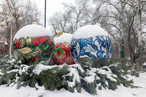 Large Christmas balls in the snow on the Christmas tree.