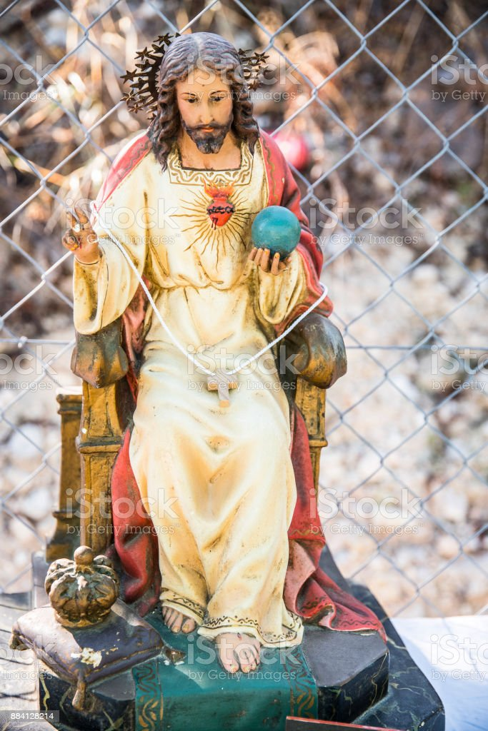 On the street and among a mesh fence the almighty son of God stock photo