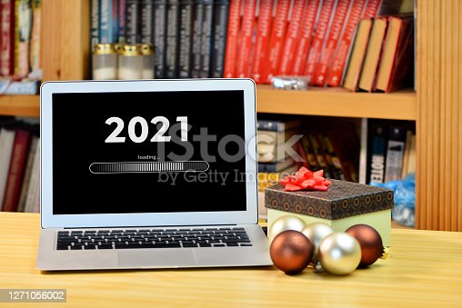 on the table christmas decorations, gift box and laptop with text - 2021 loading - on screen, blurred shelf with books in the background, Christmas concept