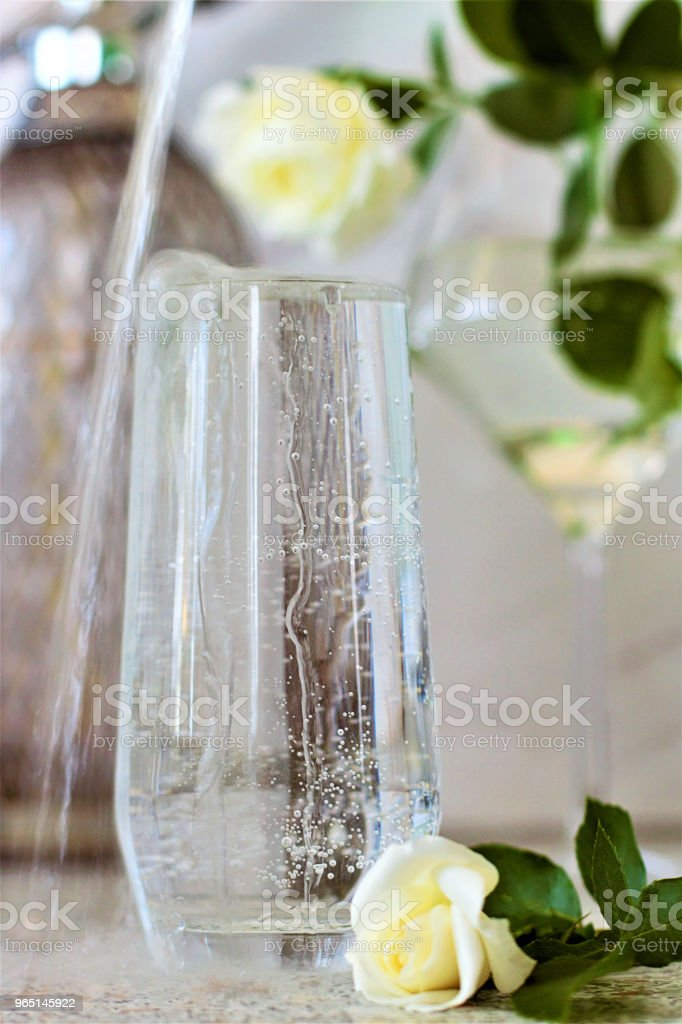 On the table is a transparent glass filled with mineral water. Still-life with white roses. royalty-free stock photo