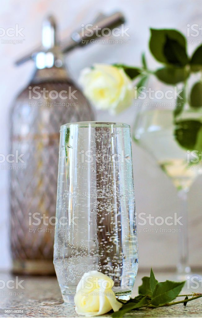 On the table is a transparent glass filled with mineral water. Still-life with white roses. zbiór zdjęć royalty-free