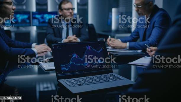 On The Table Laptop Showing Statistics Team Of Politicians Corporate Business Leaders And Lawyers Sitting At The Negotiations Table In The Conference Room Trying To Come To An Agreement Stock Photo - Download Image Now