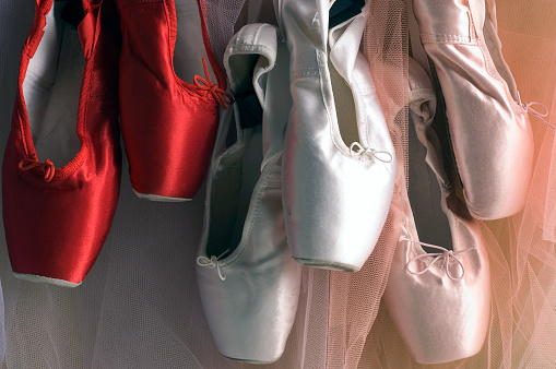 Colored pointe shoes hanging in dance studio wall.