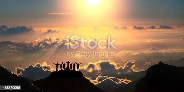 A group of people standing on a hill over the beautiful cloudscape.