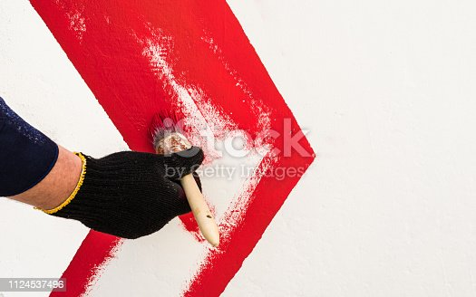 istock On the wall with red paint draws an arrow 1124537496