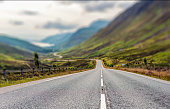 Close-up on the tarmac in the foreground on a curving downhill route towards the remote Loch Maree in Glen Docherty, in North West Scotland.