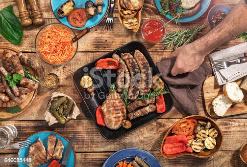 657146780 istock photo On the wooden table different food, grilled steak, sausages and grilled vegetables, top view 646085448