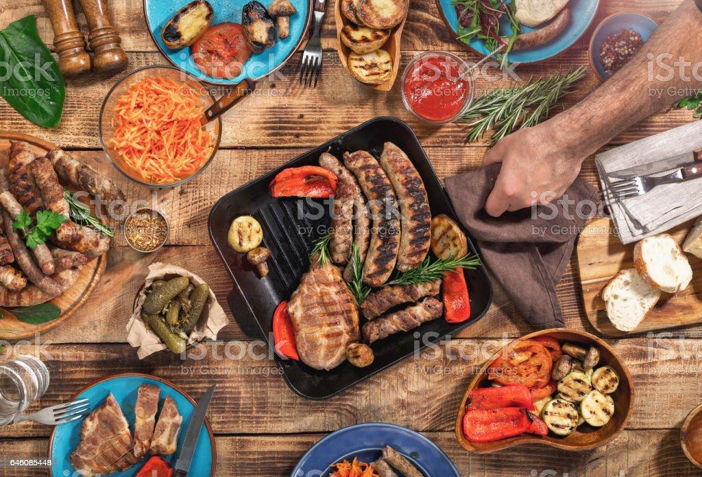 En la mesa de madera diferentes alimentos, Bistec a la plancha, embutidos y verduras a la parrilla, vista superior - foto de stock