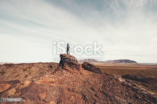 Man standing on the rock on top of Eldborg crater in Iceland.
