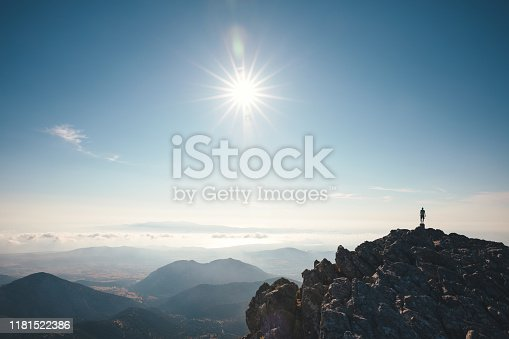 Man standing on the top of Mount Zas, which is the highest point in the Cyclades (Naxos island, Greece).