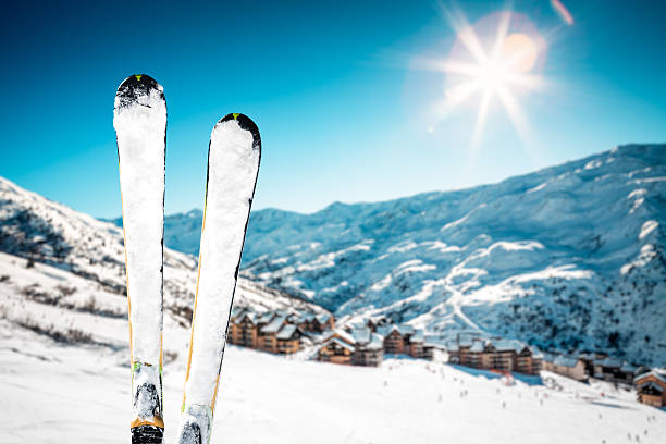 On Top Of Ski Slope Snowcapped skis on the top of ski slope. Mountain ski village in the background. ski resort stock pictures, royalty-free photos & images