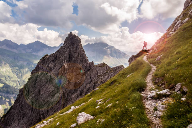 On Top of the Mountains Single Hiker on a Narrow Mountain Path in the Sunlight steep stock pictures, royalty-free photos & images