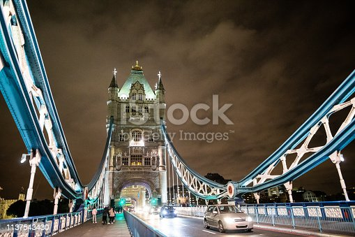 Low angle view of Tower Bridge at night, with traffic and street lights