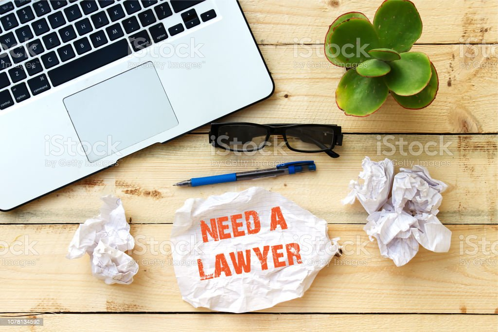 NEED A LAWYER on white paper on office wooden table stock photo