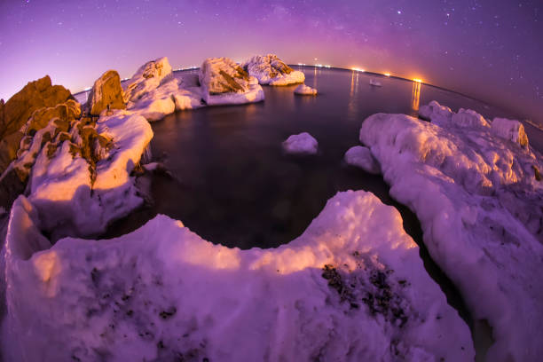 On winter nights, snow and ice cover the rocks by the sea stock photo