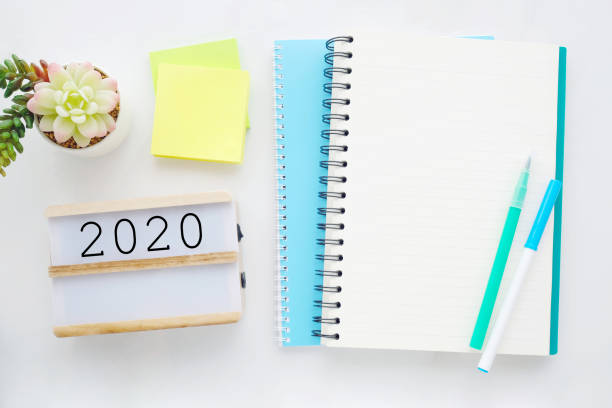 2020 on wood box, blank notebook paper on white marble table background, 2020 new year mock up, template with copy space for text, top view stock photo