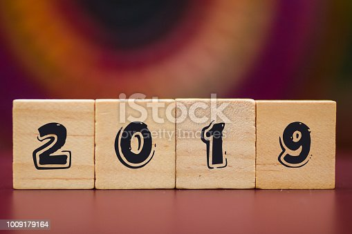 1009979852 istock photo 2019 on Wood cubes against colorful background 1009179164
