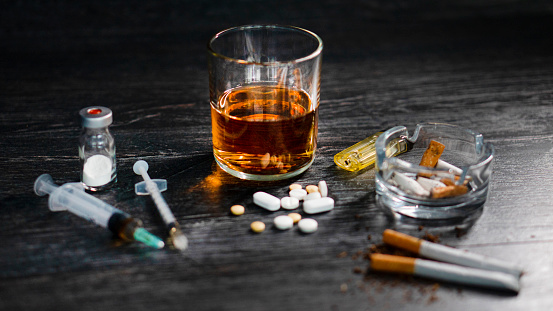 on wood table at party with alcohol and drugs or heroin, pills, gambling.