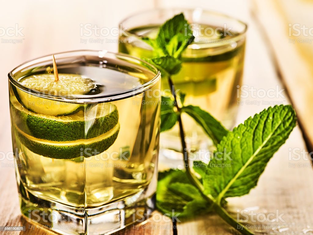 On wooden boards are glass with green drink and mint . stock photo