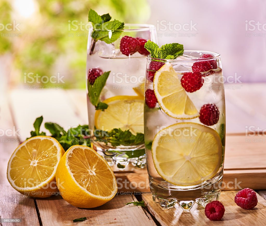 On wooden boards are glasses with raspberry mojito and lime. stock photo