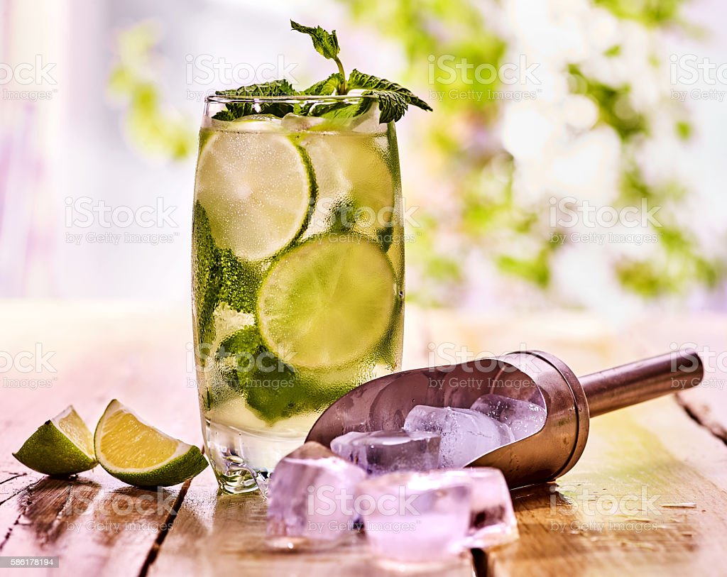 On wooden boards glass with mohito and scoop ice. stock photo