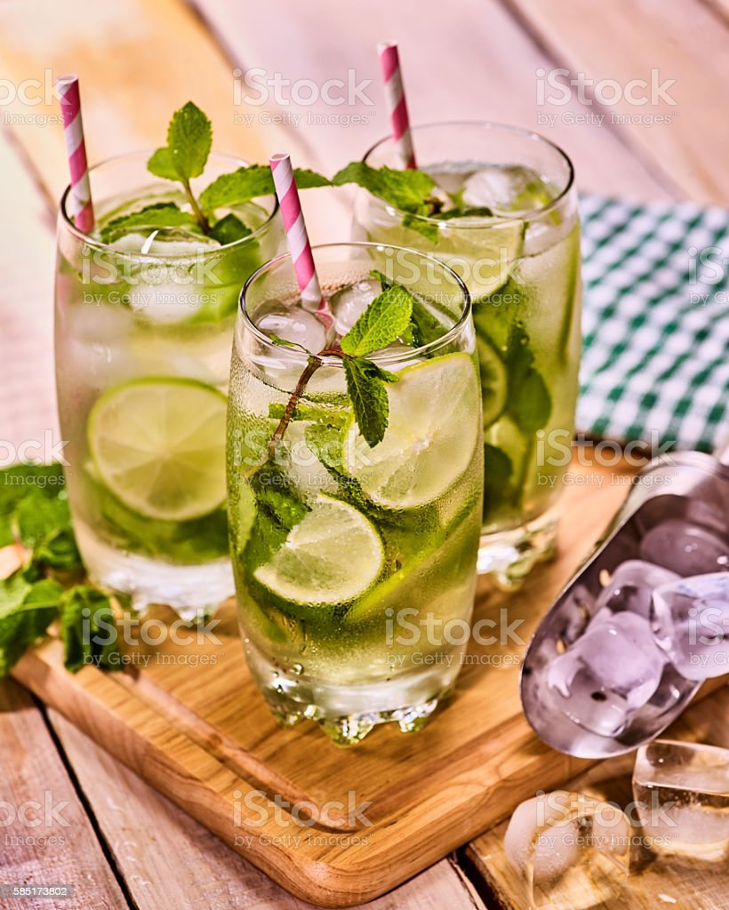 On wooden boards glasses with mohito and scoop ice. stock photo