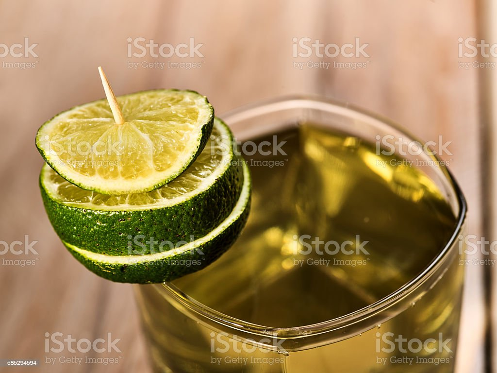 On wooden boards is glass with green drink and lime. stock photo