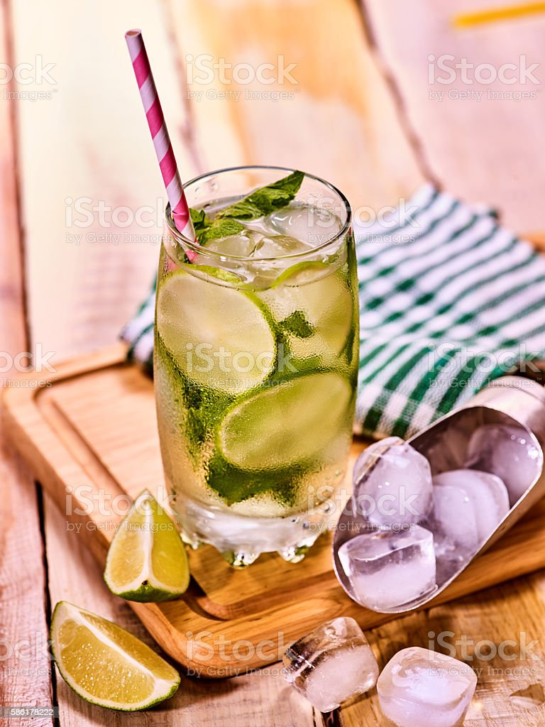 On wooden boards is glass with mohito and scoop ice. stock photo