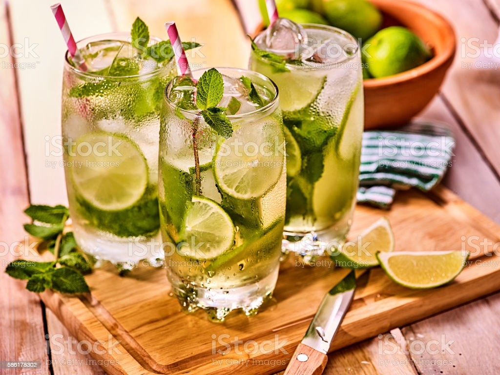 On wooden boards is glasses with mohito and knife. stock photo