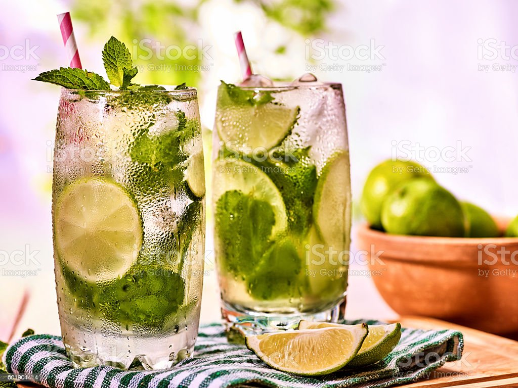 On wooden boards is glasses with mohito and napkin. stock photo