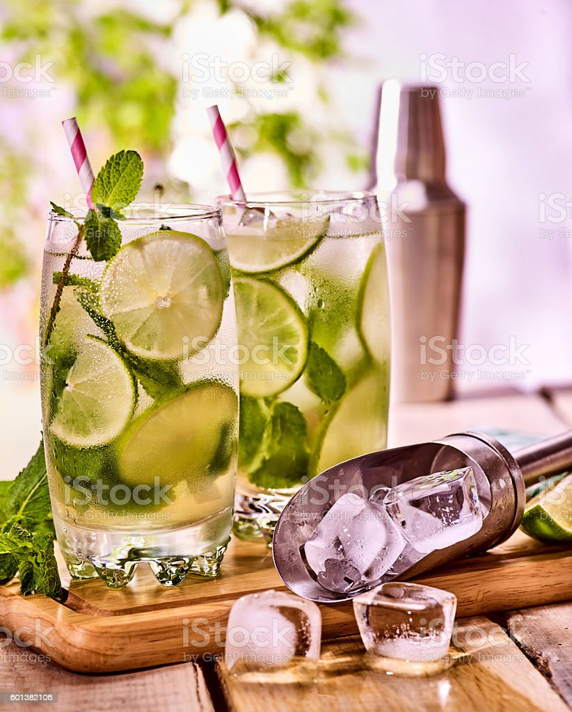 On wooden boards is glasses with mohito and shaker . stock photo