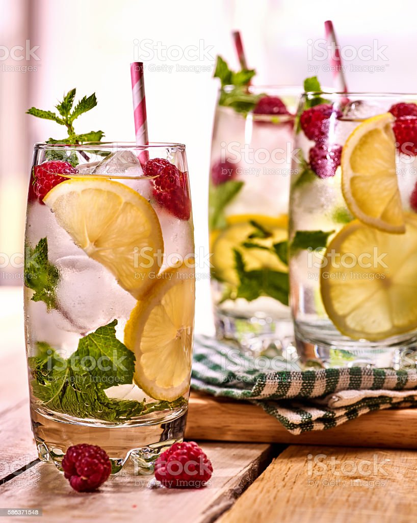 On wooden boards is glasses with raspberry mohito and lime. stock photo
