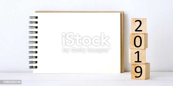 1057357020istockphoto 2019 on wooden cubes and blank notebook paper on table background, 2019 new year mock up, template with copy space for text 1060335246